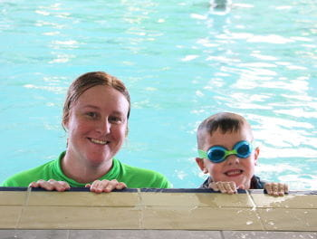 A swim instructor with a little boy by the edge of the pool
