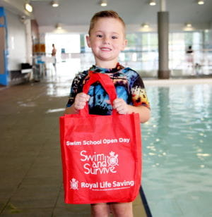 Young swimmer Jaxx holding a Swim and Survive bag