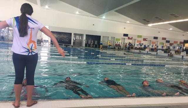 An synchro instructor by the side of the pool with a number of girls in the pool floating on their back