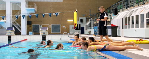 A group of Synchro WA coaches practising rescue skills in the pool watched by a Royal Life Saving trainer