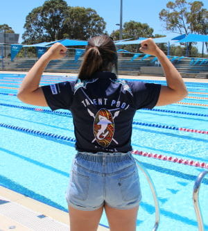 Bree Bugeja standing with back to the camera with arms in muscle pose, showing off her Talent Pool t-shirt