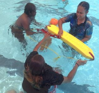 Aboriginal youth passing a lifeguard rescue tube in the pool at Jigalong