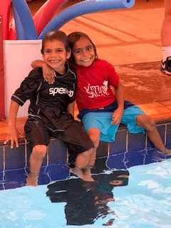 Two Martu boys with arms around each others shoulders sitting on the edge of the pool at Newman