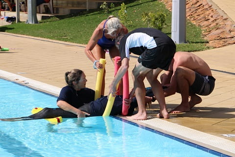 group of people practising a spinal rescue from a pool