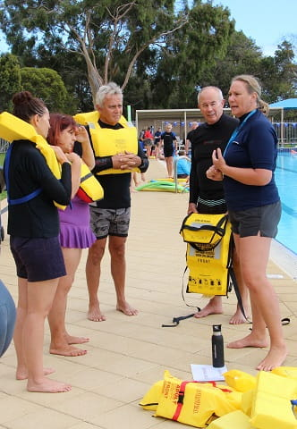 adults wearing lifejackets in training exercise at swimming pool