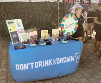 A volunteer at the Don't Drink and Drown stand during O Day