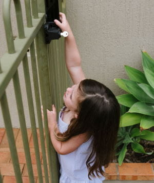 A toddler girl standing by a pool fence, reaching up to the latch.