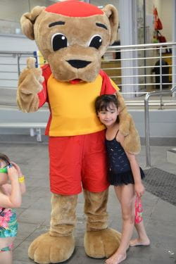 Walter with a little girl by the pool at Kwinana