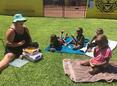 Warburton VacSwim students sitting on the pool lawn with child health nurse