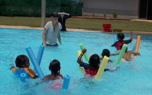 aboriginal children taking part in a pool noodle race with an instructor at Warmun Pool