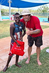 Pool manager giving swim pack to student