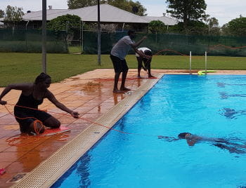 A young Aboriginal woman using a rope to rescue a course participant in the Warmun pool