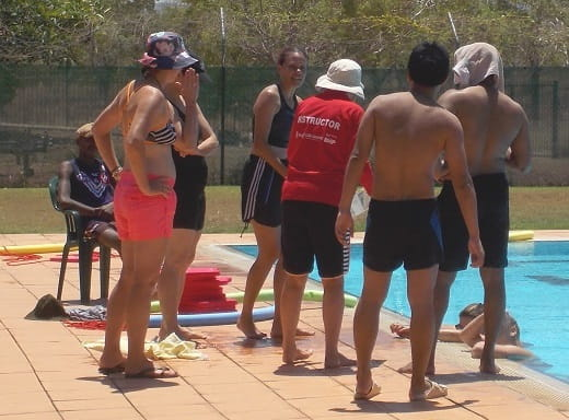 group of students next to a pool at a bronze medallion training course