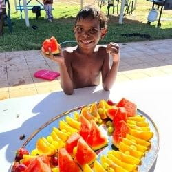 A young Aborginal boy holding fruit while standing beside a plate of fruit