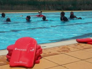 Aboriginal children int he pool with their instructor at Warmun with red kickboards by the pool