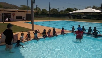 children lined up along the edge of the pool with instructor explaining what to do