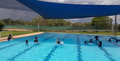 Warmun children playing water polo in their local pool as a storm rolls in