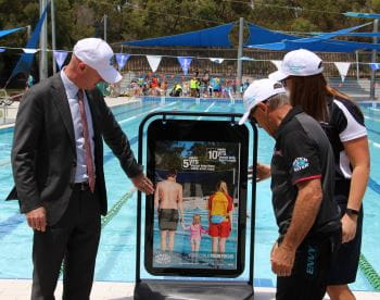 Sean L'Estrange - Member for Churchlands, LIWA President Jeff Fondacaro and Royal Life Saving's Lauren Nimmo looking at a Watch Around Water sign by the pool at Bold Park Aquatic Centre