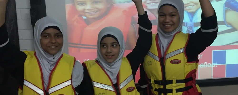3 Muslim girls wearing lifejackets