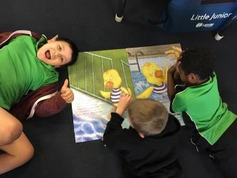 three children laying on the floor reading the Dippy Duck book, one smiling at the camera