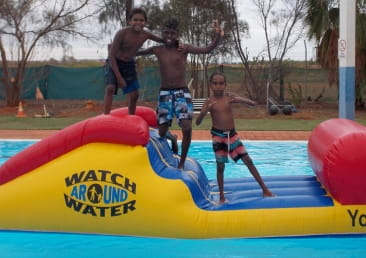3 aboriginal boys having fun on the Watch Around Water inflatable