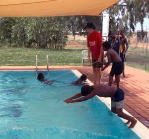 An aboriginal boy diving into the Jigalong pool with his swim instructor watching