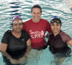 Two multicultural women in the pool with their swim instructor