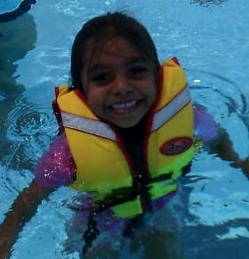 image of an Aboriginal girl wearing a lifejacket in the water and smiling at the camera