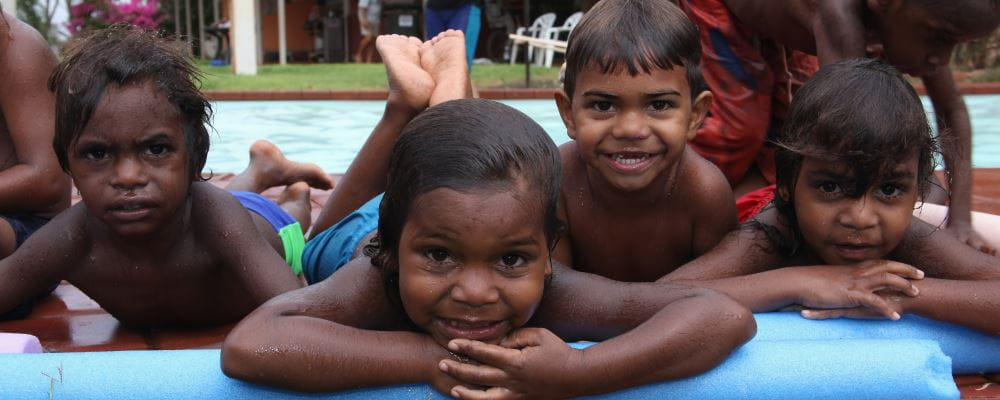 Four aboriginal boys laying by the pool at our remote pools, smiling at the camera