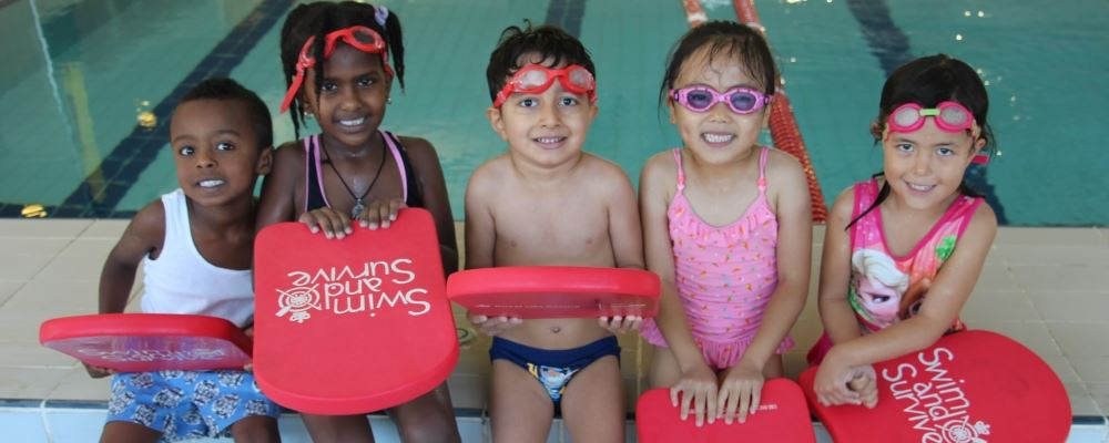 image of 5 multicultural children wearing swimming gear and sittin along the edge of a pool holding Swim and Survive kickboards