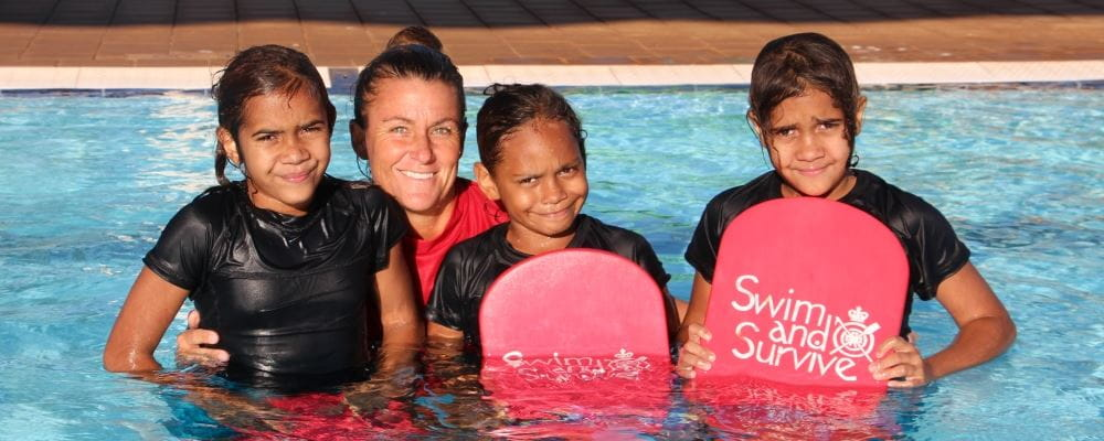 image of 3 aboriginal girls in the pool with their swim instructor and holding Swim and Survive kick boards