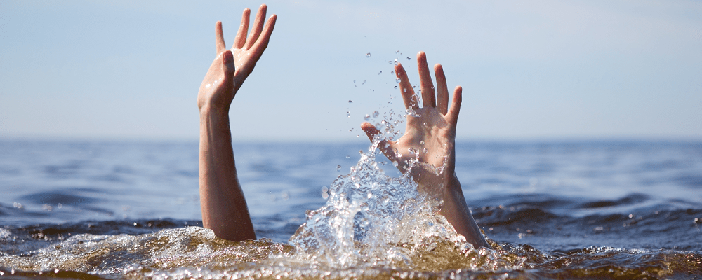 person underwater with hands up signalling for help