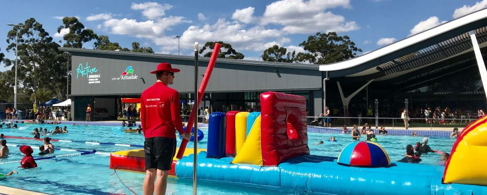 An instructor standing by the pool at Armadale Aquatic Centre with a pool inflatable and people swimming in the background