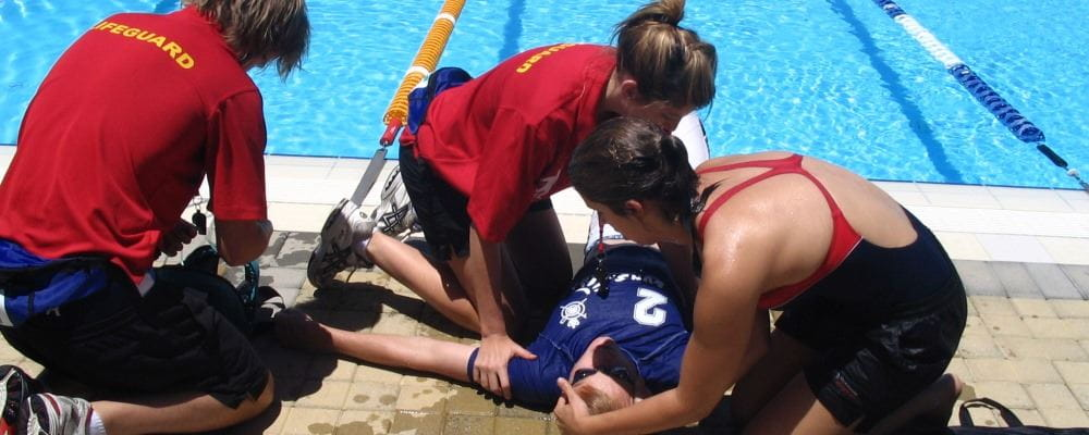 Three lifeguards performing first aid on a victim by a swimming pool