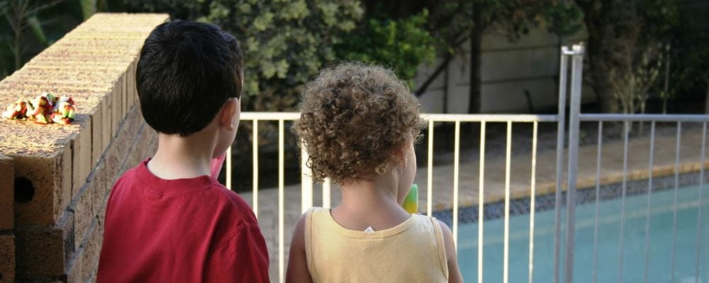 Two children standing looking through pool fence towards pool