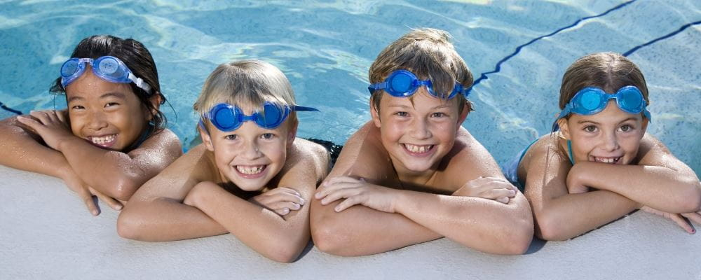 Four smiling children wearing blue goggles lean on the edge of a swimming pool