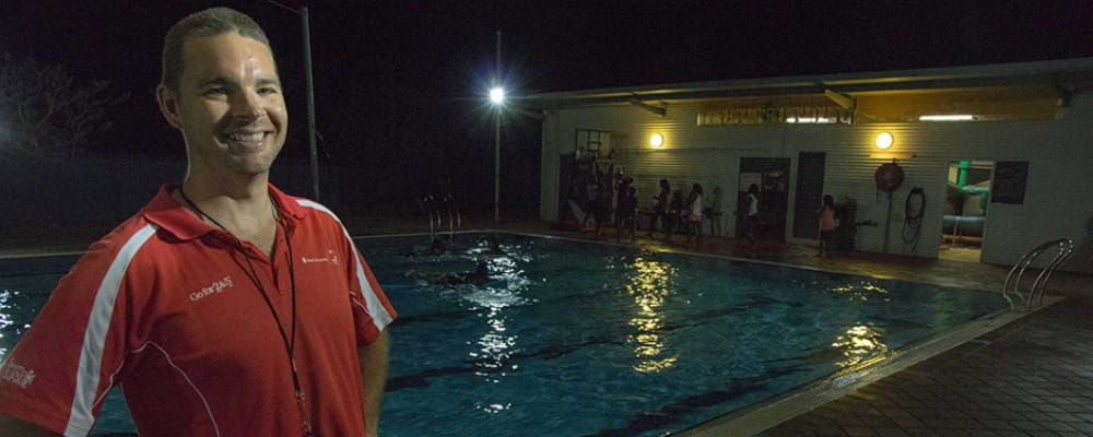 Aaron Jacobs stands in front of the Fitzroy Crossing pool at midnight