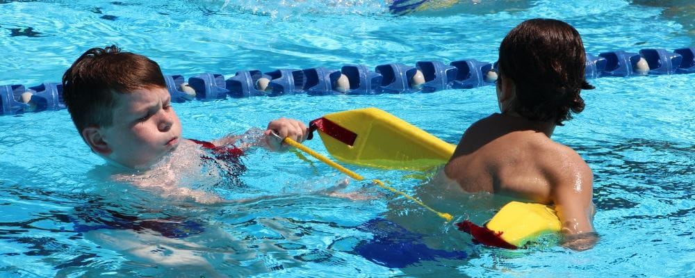 two boys in the pool practising lifesaving skills with flotation device