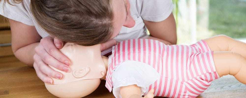a woman practising CPR on an infant manikin