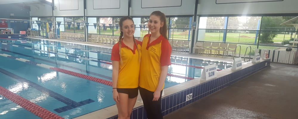 Lifeguards Jessica Colligan and Kellie Burns by the pool