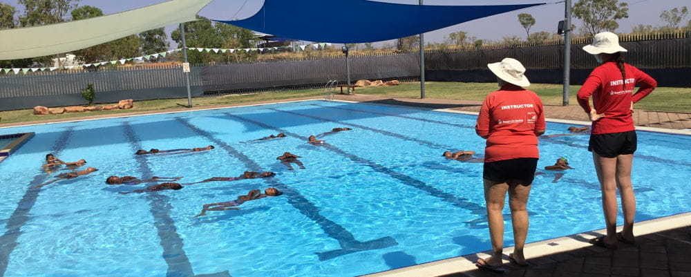 Two swim instructors by the pool watching aboriginal children float on their backs