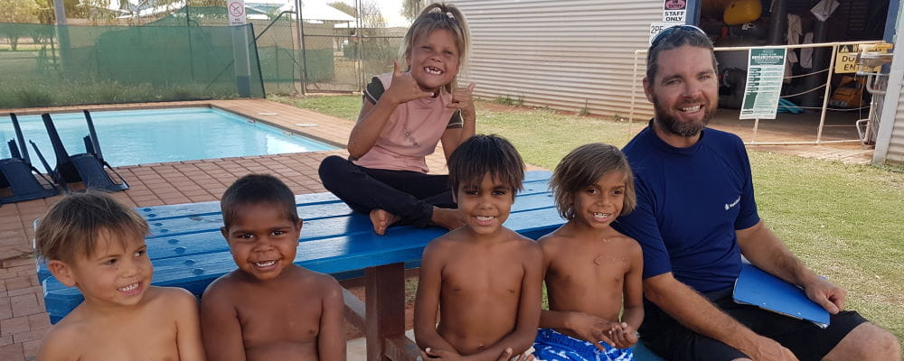 A group of Aboriginal children with Pool Manager Aaron Jacobs