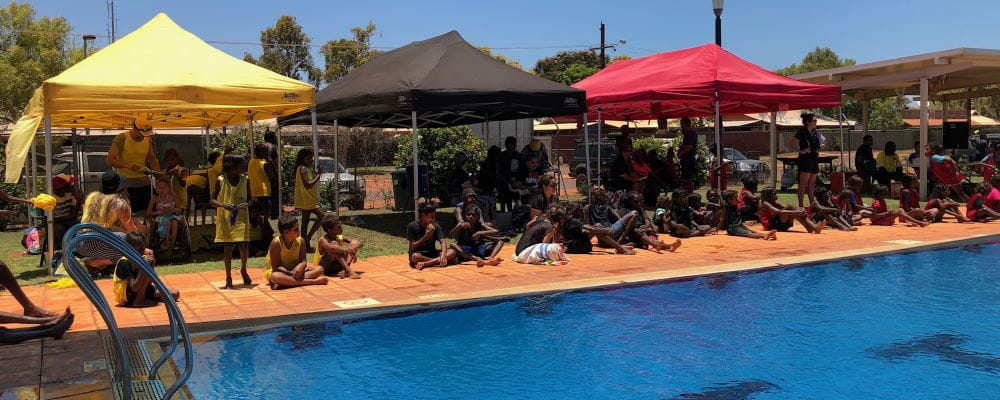 Children sitting under their yellow, black and red faction tents by  the pool at Bidyadanga