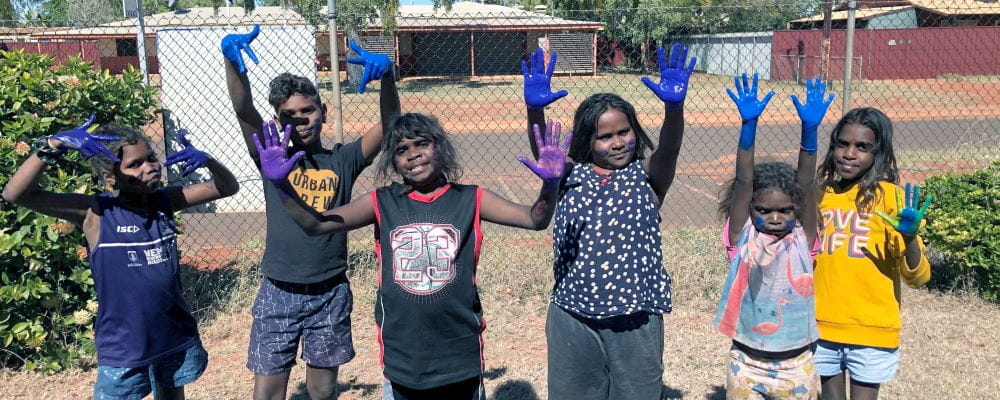 Aboriginal children with paint on their hands standing in a line smiling