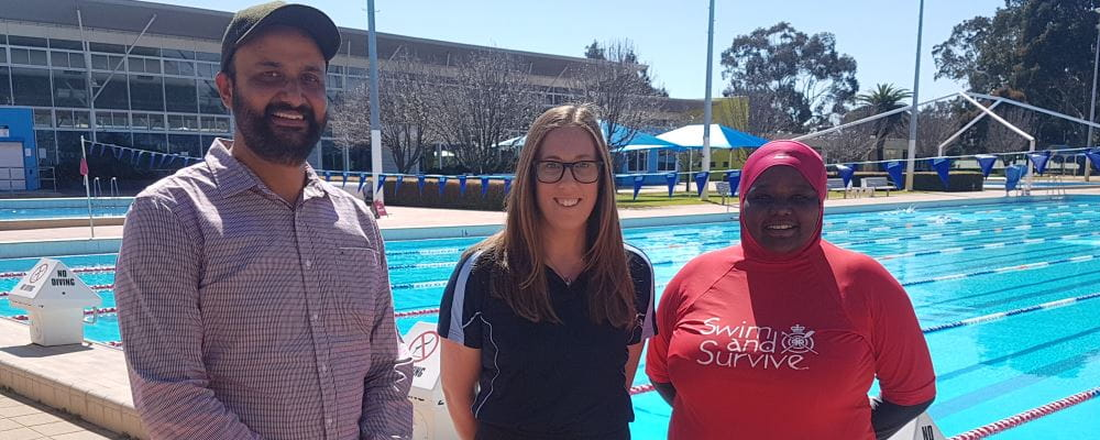 Jasjit Mann from Indian Society WA with RLSSWA's Lauren Nimmo and swim instructor Najma Ahmed by the pool at Terry Tyzack Aquatic Centre