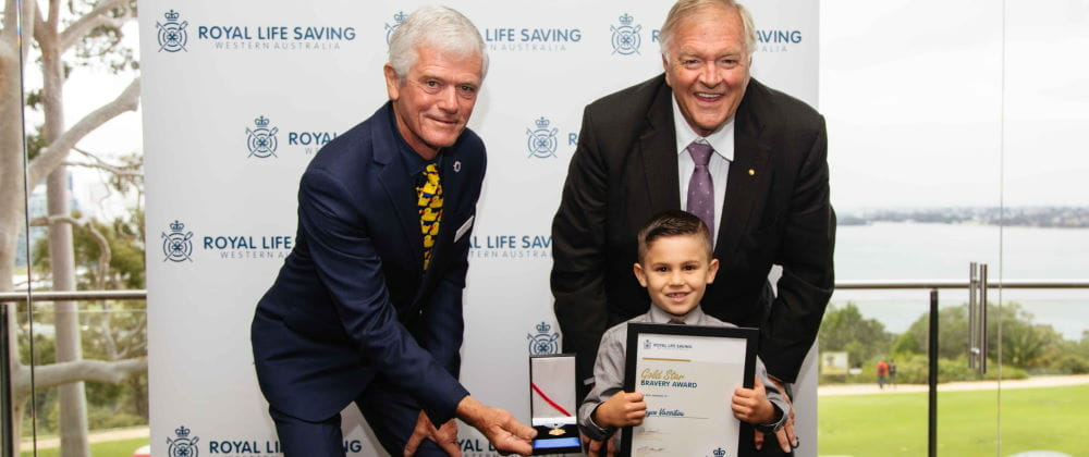 Jayce Vassiliou receiving his award from RLSSWA President Colin Hassell and WA Governor Kim Beazley