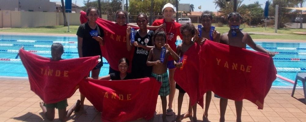 Children from Yandeyarra with Pool Manager Jacqui Forbes holding their Yande towels and trophies