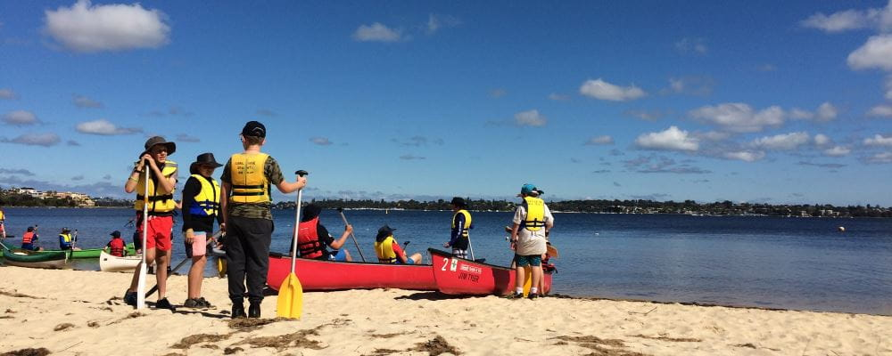 Scouts by the Swan River wearing lifejackets and getting into canoes