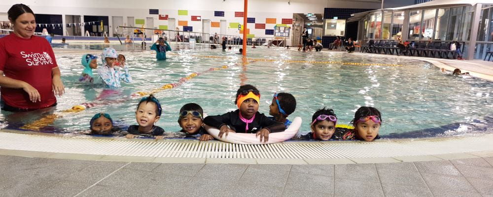 Multicultural kids along the edge of the pool with their Swim Instructor at Cannington Leisureplex