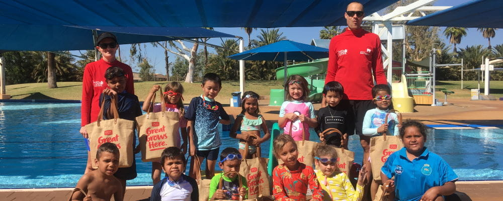 A group of children with two swim instructors standing by the pool at South Hedland holding Uncle Tobys bags